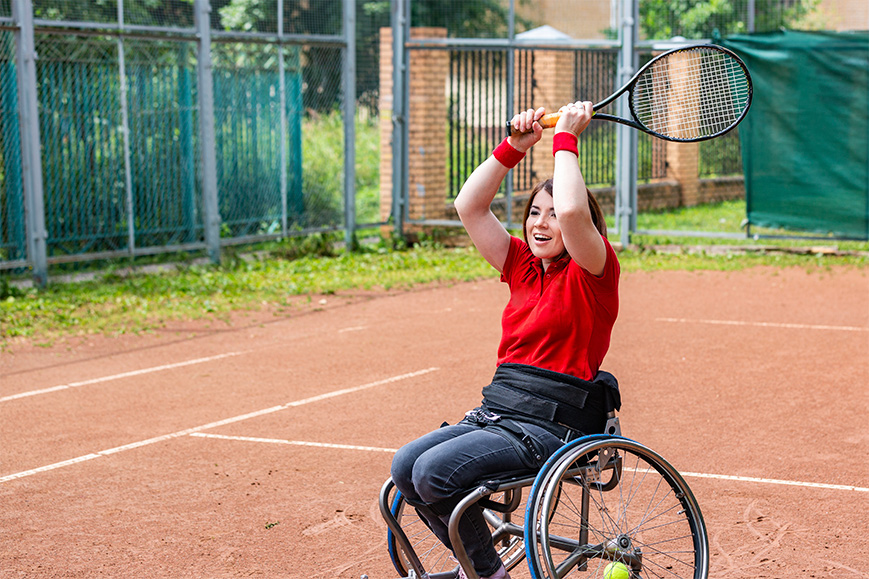 A disabled young woman in a wheelchair playing tennis on a tennis court.