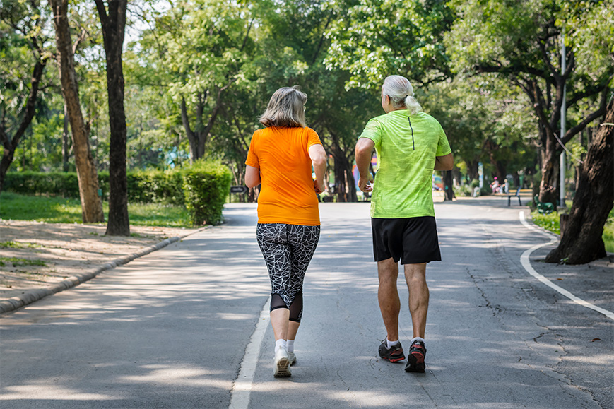 Elderly couple jogging together on a path.
