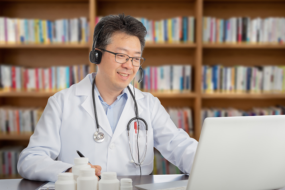 Doctor conducting a remote consultation with patient on a laptop