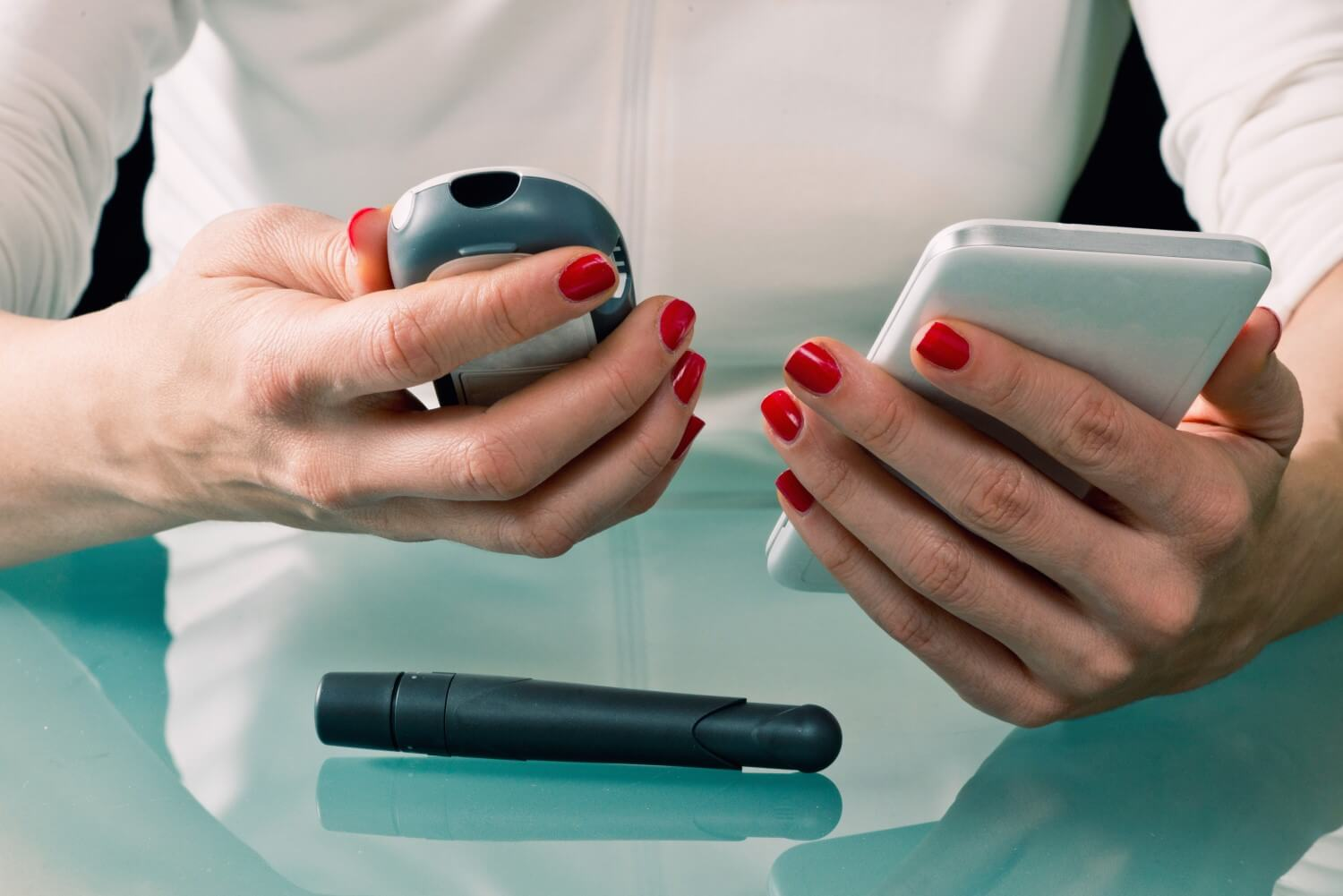 Woman using phone and blood glucose meter to manage diabetes treatment