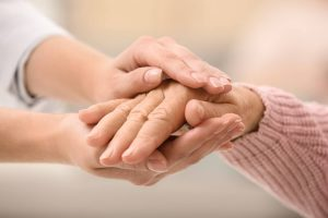 Nurse holding hands of elderly woman against blurred background